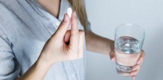 Hashimoto Behandlung - Frau mit Glas Wasser und Tablette