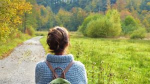 Frau vor grüner Landschaft mit Rucksack