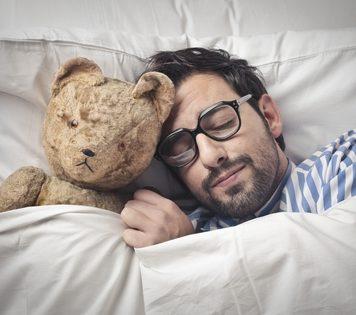 Gesunder Schlaf - Mann kuschelt mit seinem Teddy und schläft