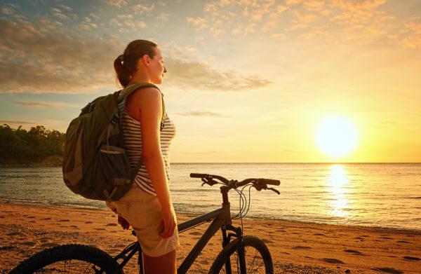 Vitamin D- Junge Frau auf Fahrrad am Meer in der Sonne