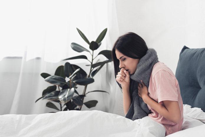 Hausmittel gegen Husten, Frau sitzt hustend im Bett
