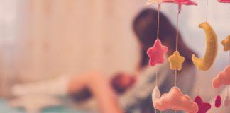 Postpartale Depression Frau mit Kind im Hintergrund verschwommen