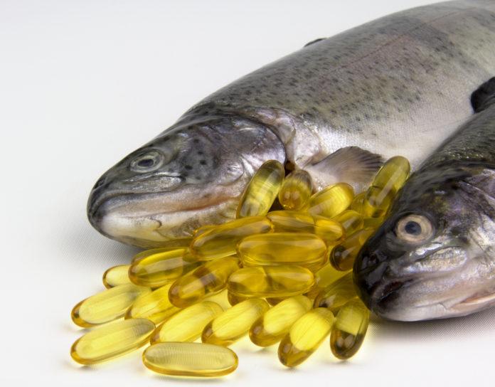 Omega 3 Fischöl Kapseln und zwei Lachse auf weißem Untergrund