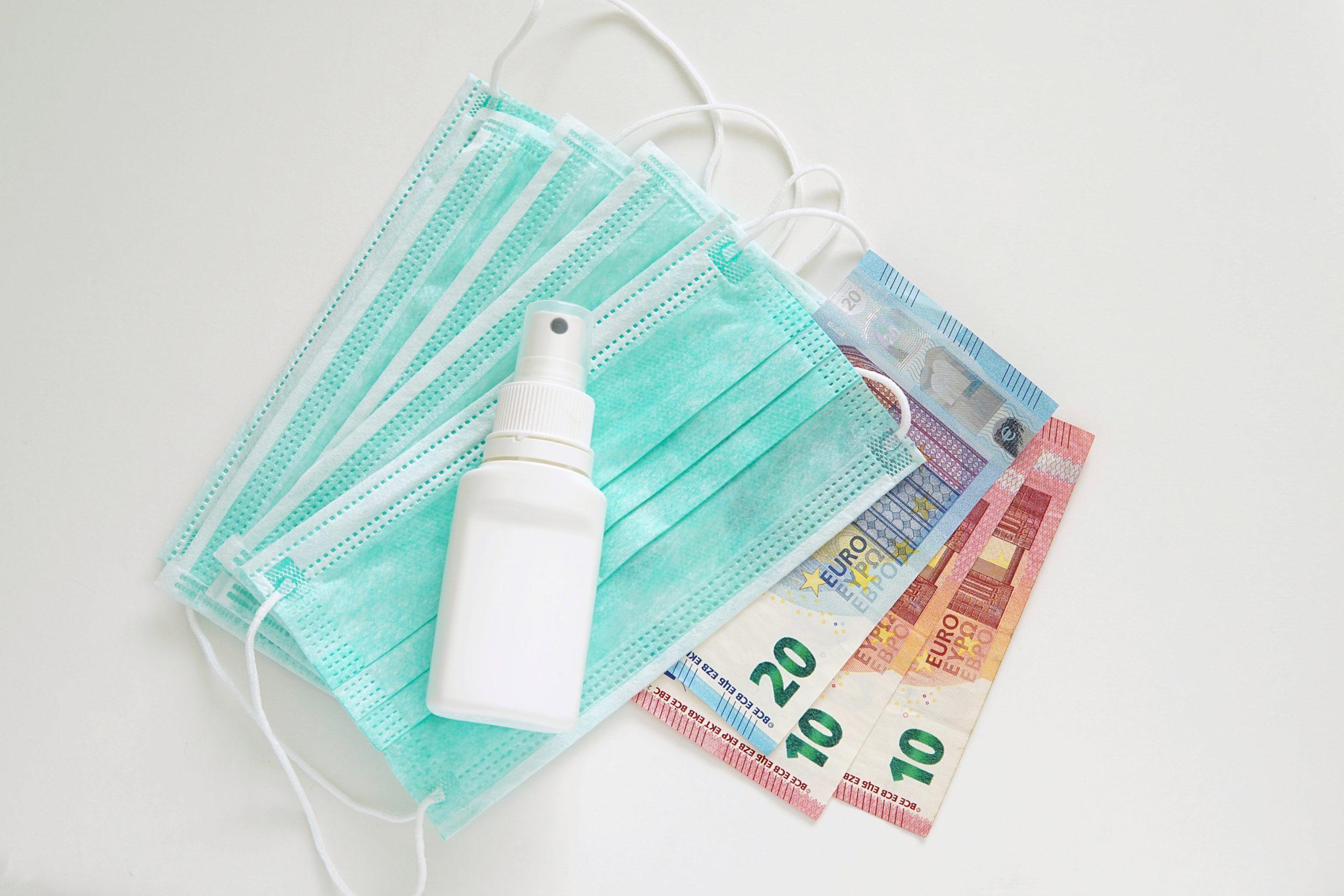 Medizinischer Mundschutz und Desinfektionsspray mit 50 Euro auf weißem Tisch