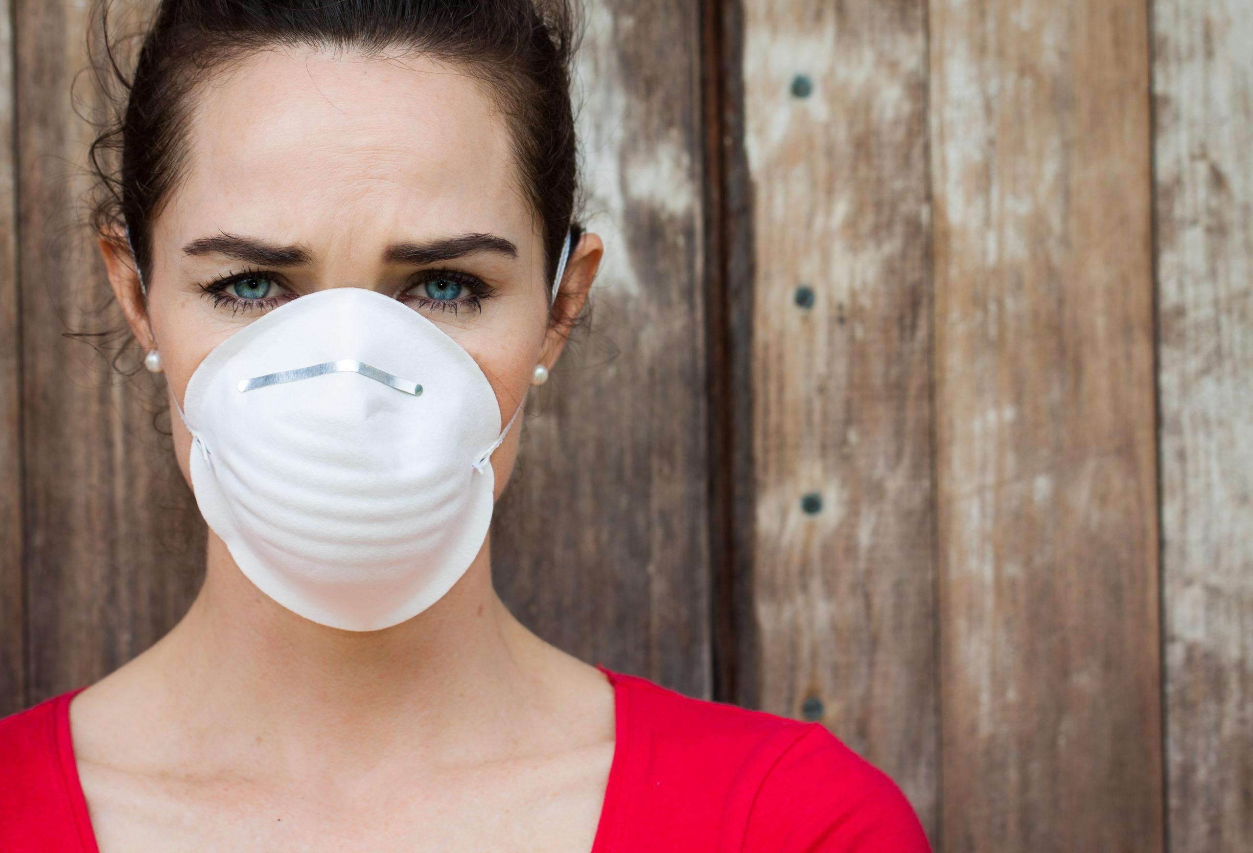 Frau mit Atemschutzmaske vor brauner Holzwand und rotem Top, sieht etwas traurig aus