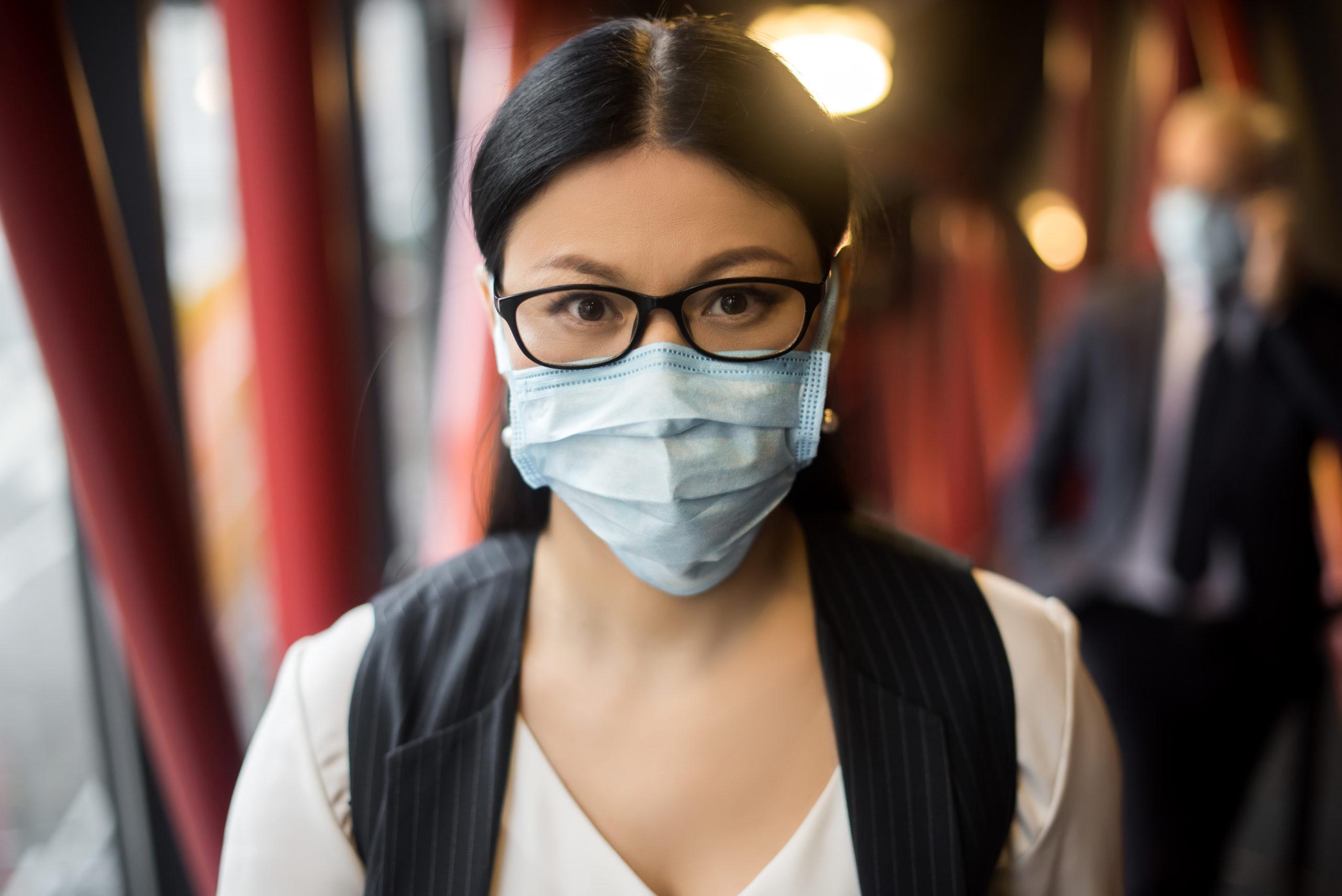 Asiatische Frau mit schwarzen Haaren und Brille mit Atemschutzmaske