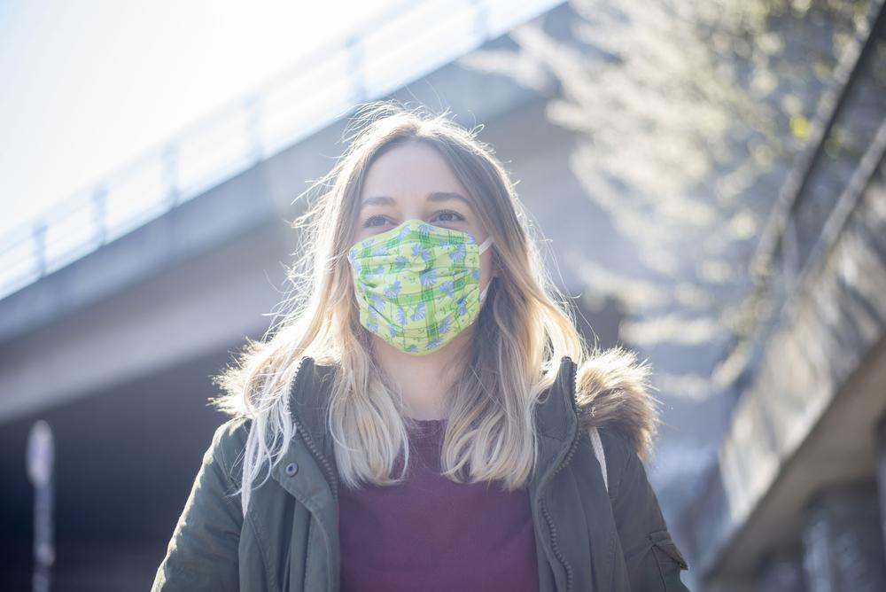 Junge Frau mit selbstgemachter Corona Atemschutz Maske im Sonnenschein in der Stadt