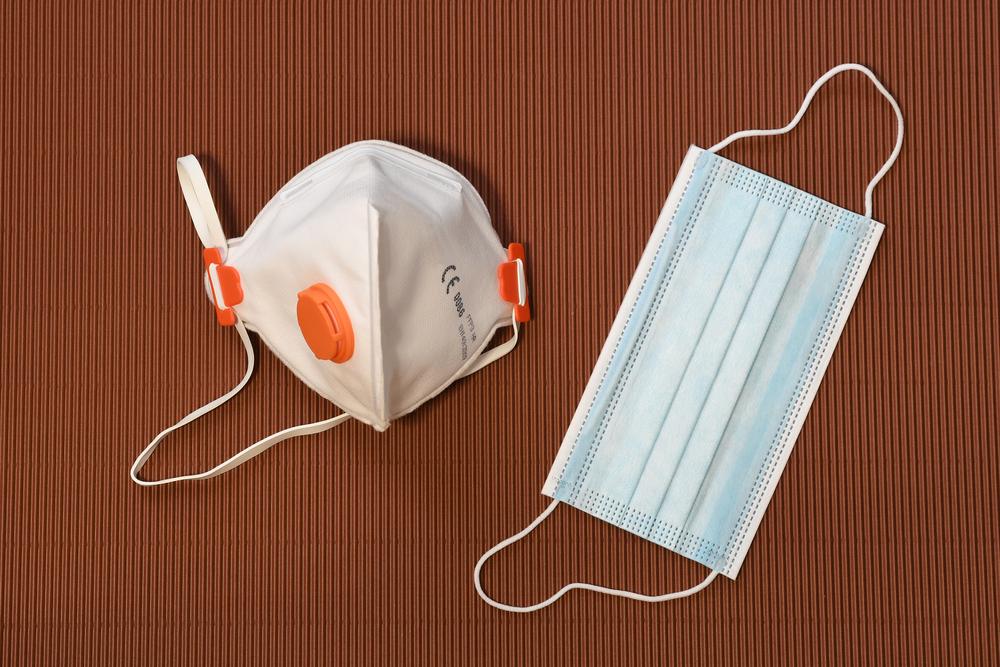 Corona Atemschutz kaufen FFP2 und medizinische Schutzmaske auf braunem Tisch